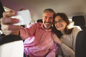 Couple taking selfie in car