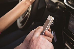 Couple using mobile phone while travelling in car