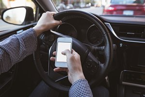 Man using mobile phone while driving car