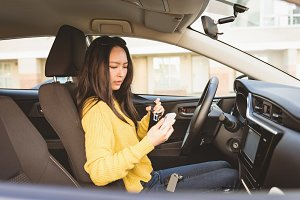 Woman using mobile phone while wearing seat belt