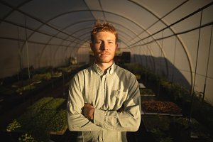 Farmer standing with arms crossed in greenhouse
