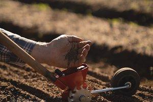Farmer putting seeds in hand tool