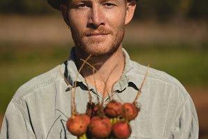 Portrait of confident farmer holding harvested turnip
