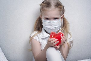 Little girl in a medical mask with a red heart in his hands. The concept of children's health
