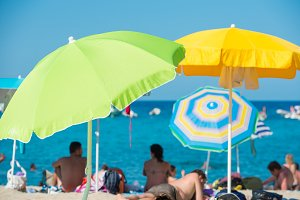 People lying under umbrellas