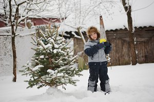 boy with saw sawing christmas tree