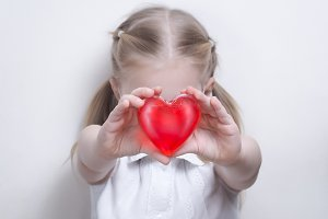 The child shows a red heart. The concept of health and medicine, funds for sick children