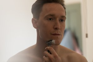 Man shaving his beard with razor