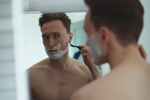 Man reflecting in mirror while shaving his beard