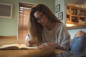 Woman writing in diary at home