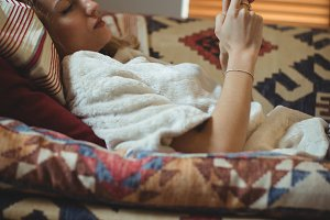 Woman using mobile phone on bed