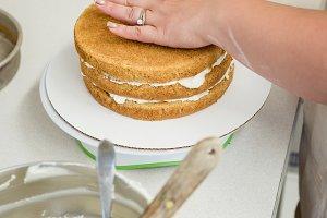 Woman preparing cake in kitchen