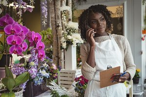 Female florist talking on mobile phone