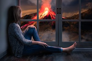 The girl looks out the window at a natural disaster - the eruption of the volcano