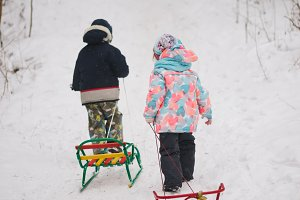 little cute girl and boy with sled