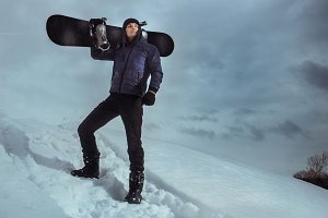Young snowboarder standing on hill and holding board for snowboarding.