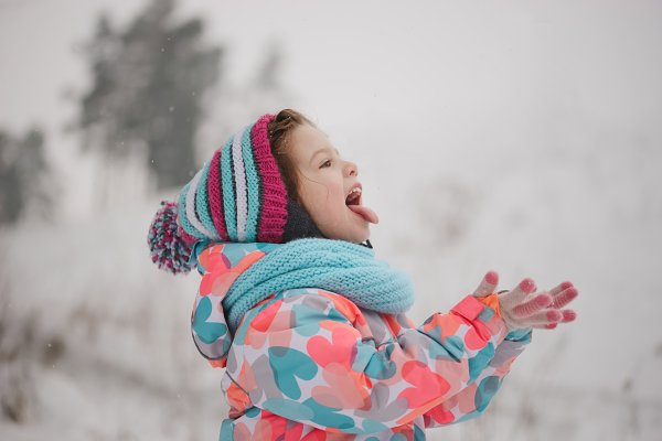 little girl catching snowflakes in…
