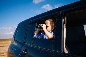 Boy travels with a binocular