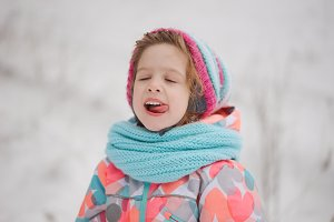 little girl catching snowflakes in winter park