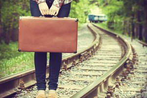 Girl with old suitcase on railway