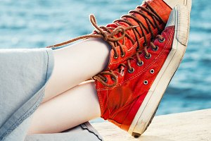 Red fashion sneakers on girl and sea