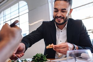 Young businessman having food