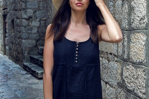 girl in hat and dress with long hair standing in Montenegro