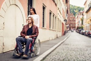 Young Couple In Wheelchair Strolling In The City