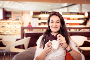 Young Woman Having Coffee In A Cafe