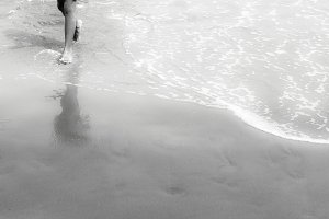 Legs walk on sand in black and white