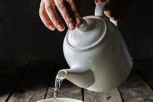 Pouring tea in white cup