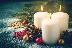 Three Christmas burning candles and decorations on dark turquoise background