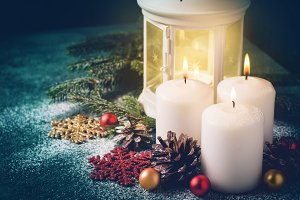 Three Christmas burning candles and lantern on dark turquoise background