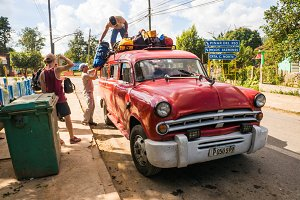 Unloading luggage from an old car