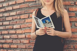 Young tourist woman in black dress standing with booklet on the brick wall background