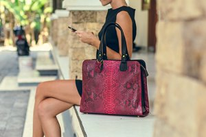 Closeup attractive beautiful woman with snakeskin python handbag posing outdoors. Bali island.