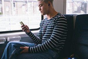 Man using mobile phone while traveling in metro