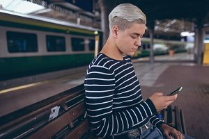 Man sitting on bench and using mobile phone