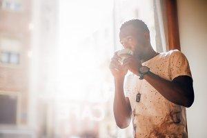 Chico negro toma café.