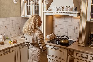 Blonde in cloak in kitchen.