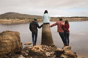 Friends relaxing near lakeside