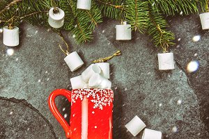 Holiday Christmas Winter concept. Red mug and Christmas tree branch with marshmallow. Black slate background, flat lay composition