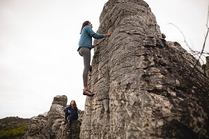 Determined woman climbing cliff