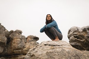 Thoughtful woman relaxing on rock