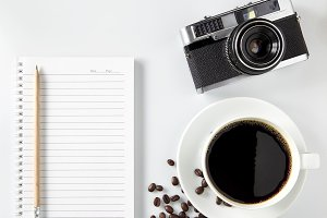 Top view of black coffee and blank notebook on white background