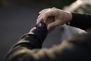 Senior man checking time on his watch