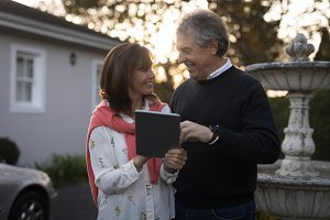 Senior couple using digital tablet outdoors