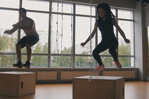 Young attractive girl and muscular man fitness instructor doing box jump exercise during a workout at the gym