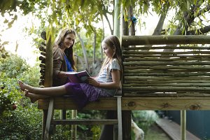 Smiling granddaughter and grandmother reading book on a tree house