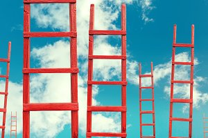 A red wooden staircase against a blue cloud of a symbol of success and achievement of set goals